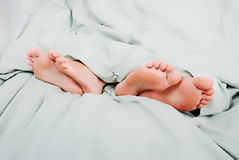 Divorcing in bed. Two pairs of legs - husband and wife are mad on each other Stock Images