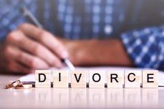 divorcio palabra de letras de madera con los anillos y de un hombre que firma el acuerdo en el fondo fotos de archivo