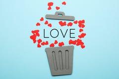 Divorzio delle coppie, cuori rossi in pattumiera Amore ed odio, separazione fotografie stock