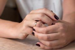 Divorzio, separazione: donna che rimuove nozze o anello di fidanzamento immagini stock libere da diritti