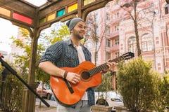Divvying musik för glad manlig gitarrist på gatan royaltyfria bilder