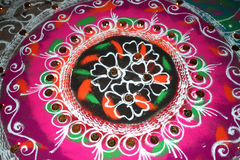 Diwali Colors. Lamps lit up in a traditional religious design made of colorful powder called Rangoli, during Diwali festival in India