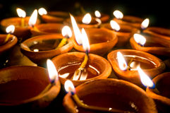 Diwali earthenware oil lamps, diyas. Shots of earthenware lamps filled with oil and with a cotton wick. These diyas are lit during diwali and other celebrations Stock Image