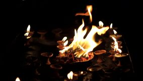 Diwali holiday. a plate with burning flowers in the background of small burning candles in clay stands in the dark. A Diwali holiday. a plate with burning stock video footage