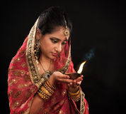 Diwali Indian woman with oil lamp. Beautiful young Indian woman in traditional sari dress holding a diwali oil lamp light, on black background