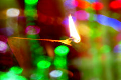 Diwali Lamp and Colors. A traditional earthen Diwali lamp lit behind a string of colorful light bulbs in blur Stock Photo
