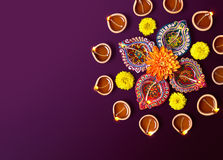 Diwali Oil Lamp. Colorful clay diya lamps with flowers on purple background Royalty Free Stock Photography