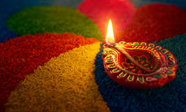 Diwali oil lamp. Diya lamp lit on colorful rangoli