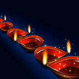 Diwali oil lamps over dark blue background Stock Photo