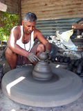 Diwali Potter. An Indian potter making a traditional diwali pot meant for rituals on his wheel on the eve of the festival