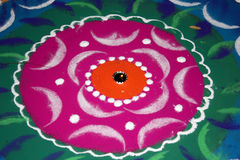 Diwali Rangoli Colors. A lamp lit in between a traditional design made of colorful powder called Rangoli, on the occassion of Diwali festival in India