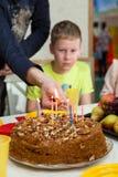 Dix années de fils faisant le souhait tandis que le père applique le match aux bougies sur le gâteau d'anniversaire Photographie stock