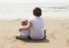 Dix ans avec le frère de bébé s'asseyant sur la plage Photographie stock libre de droits