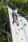 Dix ans de garçon escaladant le mur artificiel extérieur avec les prises colorées modernes Photo stock
