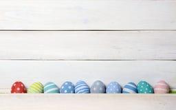 Dix oeufs de pâques faits main colorés ont aligné dans une rangée sur sur le fond en bois blanc style plat de configuration Photos libres de droits