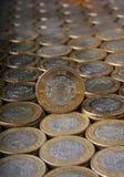 Dix pesos mexicains inventent au-dessus de plus de pièces de monnaie alignées et empilées Photos libres de droits