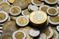 Dix pesos mexicains inventent sur une pile des pièces de monnaie mexicaines Photographie stock libre de droits