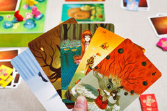 Dixit game cards in hand Royalty Free Stock Images