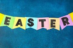 Diy复活节诗歌选兔宝宝,旗子复活节做了纸蓝色背景 礼物想法,装饰春天,复活节 库存照片