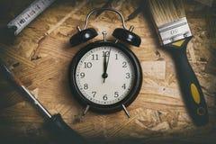DIY时间概念 围拢一个黑闹钟的工具 免版税图库摄影