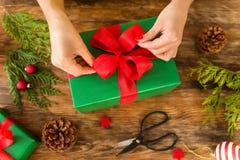 DIY礼品包装材料 包裹在土气木桌上的妇女美好的圣诞礼物 顶上看法圣诞节包裹 库存照片