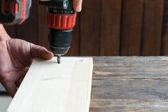 Diy -一个人的手使用一把螺丝刀的在木材料 免版税库存照片