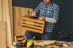 做木板箱的木匠在小企业木制品车间 库存照片
