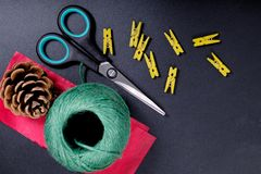 DIY background concept DIY tools scissors, green wood clip, string, pine corn and red paper on black background. With copy space Royalty Free Stock Photos