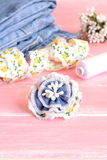 DIY Beautiful flower brooch from old jeans. Recycle jeans accessory. Jeans, lace, thread, needle on pink wooden background Royalty Free Stock Images