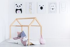 DIY bed in kid`s bedroom. Creative pillows and bedding on DIY bed in kid`s bedroom with animal drawings on white wall stock image