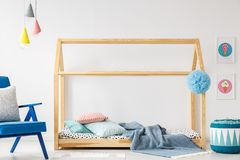DIY bed made of wood, pillows and blanket, lamps, blue armchair,. Pouf and ice-cream posters in a kid`s room interior Royalty Free Stock Photos