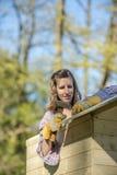 DIY-begrepp - ung kvinna som rymmer en hammare som arbetar på ett träp royaltyfri fotografi