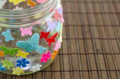 DIY candleholder closeup on a wooden table. Closeup of a DIY candleholder decorated with colorful butterflies on a wooden table Royalty Free Stock Photography