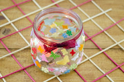 DIY candleholder on a wooden table. DIY candleholder decorated with colorful butterflies on a wooden table Royalty Free Stock Photography
