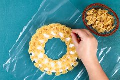 Diy Christmas pasta wreath on blue background. Gift idea, decor Christmas, Xmas, New Year. Step by step. Top view. Process kid children craft. Workshop royalty free stock images