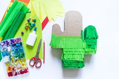 Diy cinco de mayo Mexican Pinata cactus made cardboard and crepe paper your own hands on a white background. Gift idea, decor, game cinco de mayo. Step by step royalty free stock images