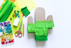 Diy cinco de mayo Mexican Pinata cactus made cardboard and crepe paper your own hands on a white background. Gift idea, decor, game cinco de mayo. Step by step royalty free stock photo
