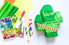 Diy cinco de mayo Mexican Pinata cactus made cardboard and crepe paper your own hands on a white background. Gift idea, decor, game cinco de mayo. Step by step stock images
