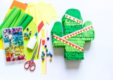 Diy cinco de mayo Mexican Pinata cactus made cardboard and crepe paper your own hands on a white background. Gift idea, decor, game cinco de mayo. Step by step royalty free stock image
