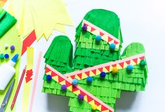 Diy cinco de mayo Mexican Pinata cactus made cardboard and crepe paper your own hands on a white background. Gift idea, decor, game cinco de mayo. Step by step royalty free stock photos