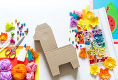 Diy cinco de mayo Mexican Pinata llama made cardboard and crepe paper your own hands on a white background. Gift idea, decor, game cinco de mayo. Step by step stock photography
