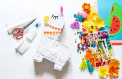 Diy cinco de mayo Mexican Pinata llama made cardboard and crepe paper your own hands on a white background stock photo