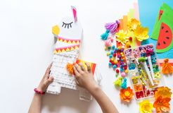 Diy cinco de mayo Mexican Pinata llama made cardboard and crepe paper your own hands on a white background. Gift idea, decor, game cinco de mayo. Step by step royalty free stock photo