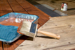 Diy concept of varnishing a floor. Diy concept of varnishing a wooden floor or exterior deck with a plastic tray and paintbrush on the corner angle with only one Royalty Free Stock Image