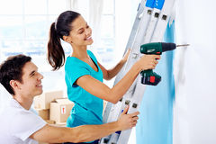 Diy couple. Couple drilling in wall doing diy at new home after moving in together stock photo