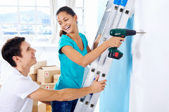 Diy couple. Couple drilling in wall doing diy at new home after moving in together Royalty Free Stock Photos