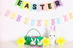 Diy decor for Easter. Paper garlands, vase bunny, daffodils, eggs bunnies, basket with painted eggs royalty free stock image