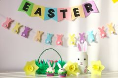 Diy decor for Easter. Paper garlands, vase bunny, daffodils, eggs bunnies, basket with painted eggs stock image
