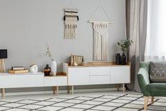 DIY-dekor på väggen ovanför vitskåp i vardagsruminteri arkivbild