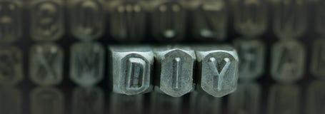 DIY deletreó del sacador del alfabeto del sello del metal, palabras de DIY representa lo hace usted mismo Imagen de archivo
